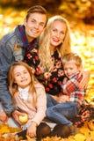 Близкое поднимающее вверх фото жизнерадостных родителей и детей сидя в парке осени стоковое изображение