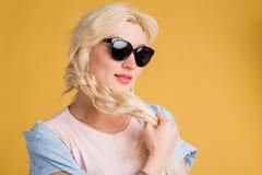 Близкое поднимающее вверх фото красивой женщины в солнечных очках на желтой предпосылке стоковое изображение rf