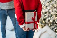 Близко вверх, девушка в свитере santa получает готовой дать подарок и парень ждет стоковое изображение rf