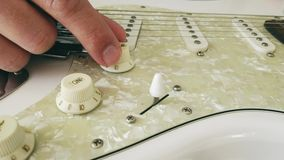 Близко вверх руки гитариста регулируя тон и регуляторы звука на электрической гитаре акции видеоматериалы