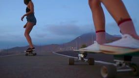Близко - вверх скейтборда и 2 девушек который едут на досках от горы на предпосылке утесов и неба медленно сток-видео