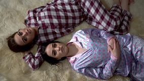 2 близнеца сестер в пижамах лежат на мягком ковре смотря на один другого и имея прекрасную выравниваясь беседу отношение акции видеоматериалы