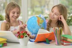 2 близнеца сестер делая домашнюю работу Стоковые Изображения