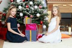 Близнецы девушек с рождественской елкой подарков e Стоковое фото RF