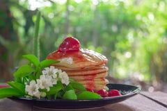 Блинчики домодельные с отбензиниванием соуса клубник служили со свежими белыми цветками на черной плите на таблице в доме сада стоковые фото
