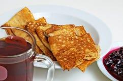 Блинчики и варенье вишни с чаем для завтрака Стоковая Фотография