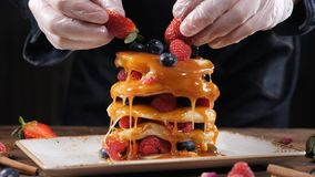 Блинчики с карамелькой покрывая с ягодами на верхней части Сладкая концепция еды и десерта Шеф-повар в перчатках украшая блинчики акции видеоматериалы