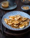 Блинчики с медом, бананами и гайками сосны Стоковые Изображения RF