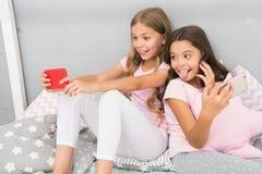 Блоггеры smartphone девушек маленькие Онлайн развлечения Исследуйте социальную сеть Smartphone для развлечений малыши стоковое фото