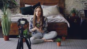 Блоггер милой девушки популярный записывает видео о цветках дома при камера сидя на поле около двуспальной кровати в славном сток-видео