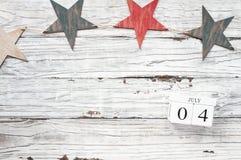Блоки календаря 4-ое июля против деревенской предпосылки со звездами стоковая фотография