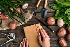 Блокнот для входов в женские руки, конец-вверх Взгляд сверху на деревянной предпосылке с садовыми инструментами, зеленых цветах,  Стоковое Фото
