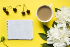 Блокнот для пиона текста белого цветет чашка кофе ягод вишни на желтой яркой предпосылке Стоковая Фотография