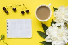 Блокнот для пиона текста белого цветет чашка кофе ягод вишни на желтой яркой предпосылке Стоковое фото RF