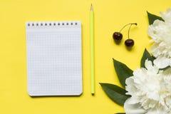 Блокнот для ягод вишни пиона белых цветков текста на желтой яркой предпосылке Стоковые Фото