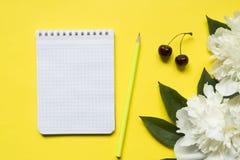 Блокнот для ягод вишни пиона белых цветков текста на желтой яркой предпосылке Стоковые Фотографии RF