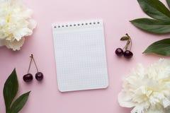 Блокнот для ягод вишни пиона белых цветков текста на предпосылке пастельного пинка Стоковые Изображения