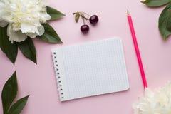 Блокнот для ягод вишни пиона белых цветков текста на предпосылке пастельного пинка Стоковое Фото