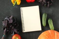 Блокнот и состав овощей на черной доске стоковые фотографии rf