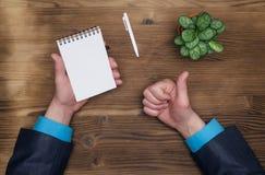 Блокнот при лист бумаги пустой страницы и рука бизнесмена показывая большие пальцы руки вверх Сделать список Стоковая Фотография RF