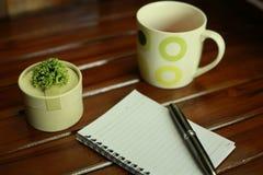 блокнот, ручка, монетки и украшение изолированные на деревянной предпосылке Стоковое Фото