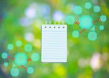 Блокнот с диаграммой на предпосылке дерева расплывчатой используя обои или для образования, фото дела Примите примечание продукта Стоковые Изображения