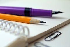 Блокнот с карандашем и ручкой стоковые изображения