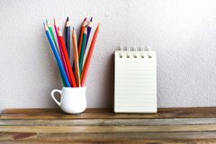 Блокнот с карандашем на деревянной предпосылке доски используя обои для образования, фото дела Примите примечание продукта для кн Стоковая Фотография RF