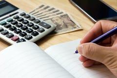 Блокнот с ручкой, калькулятором, умным телефоном, japnese банкнотой иен стоковые фотографии rf