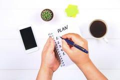 Блокнот с текстом: план Белая таблица с телефоном, кактусом, бумагой для примечаний, кружкой кофе Руки держат тетрадь и ручку Стоковые Фото