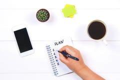 Блокнот с текстом: план Белая таблица с телефоном, кактусом, бумагой для примечаний, кружкой кофе Руки держат тетрадь и ручку Стоковое Изображение