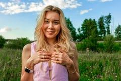 Блондинка весны в природе с зеленой травой с глубоким расщеплением покрывает ее комод с ее руками стоковое фото rf