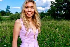 Блондинка весны в природе с зеленой травой с глубоким neckline половина поворота и покрывает ее комод с ее руками стоковое изображение rf