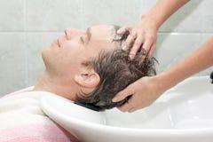 Блондинка в салоне получая помыт ее волосам с sha Стоковое Изображение RF
