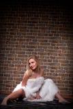 блондинка в шерсти на кирпиче стены Стоковое фото RF