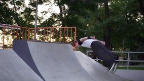 Блондинка в широких черных штанах и красная бинта на волосах делает красивый сомерсо, бегущий по скейту видеоматериал