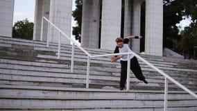 Блондинка в широких черных штанах и красный бинт на волосах делает приятный флип по лестничным перилам на улице видеоматериал