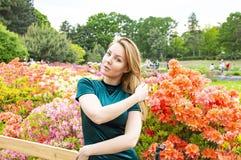 Блондинка девушки на предпосылке цветков в парке стоковая фотография rf