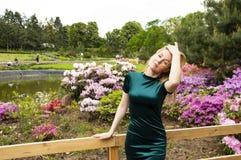 Блондинка девушки на предпосылке цветков в парке стоковое изображение