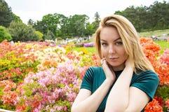 Блондинка девушки на предпосылке цветков в парке стоковое фото rf
