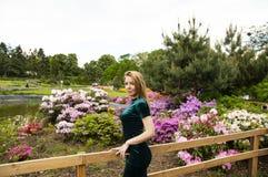 Блондинка девушки на предпосылке цветков в парке стоковые изображения rf