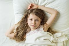 Блондинка девушки ребенка с длинными волнистыми волосами с стороной ангела просыпает вверх и усмехается на камере лежа на подушке Стоковая Фотография RF