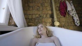 Блондинка красивой девушки сексуальная в утре представляя в bathroom E Молодая белокурая женщина лежа в ванне в акции видеоматериалы