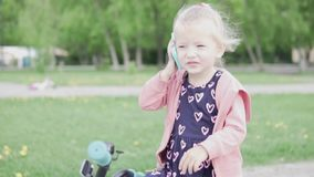 Блондинка маленькой девочки говоря по телефону игрушки сток-видео