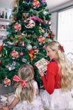 Блондинка мамы и дочери со смычками, сидящ на ели рождества и украсить ее стоковые изображения