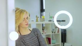 Блондинка смотрит в зеркале сток-видео