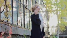 Блондинка со стеклами говорит по телефону видеоматериал