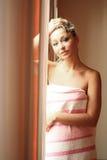 блондинка стоит детеныши окна стоковое изображение