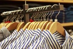 Блузки на вешалке в бутике одежд женщин стоковые фотографии rf