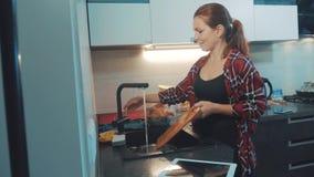 Блюда девушки моя в разделочной доске кухни смотря цифровой планшет Кашевары женщины в кухне девушка моет a видеоматериал